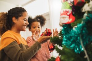 parent helping their child decorate a tree