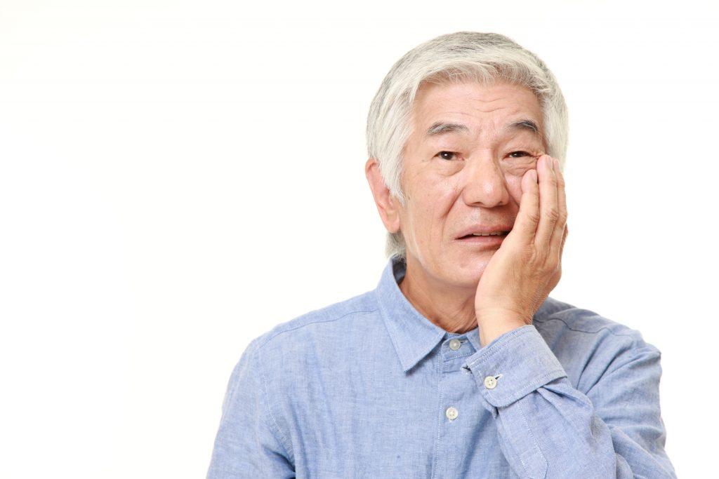 older man experiencing dental implant sensitivity in Arlington