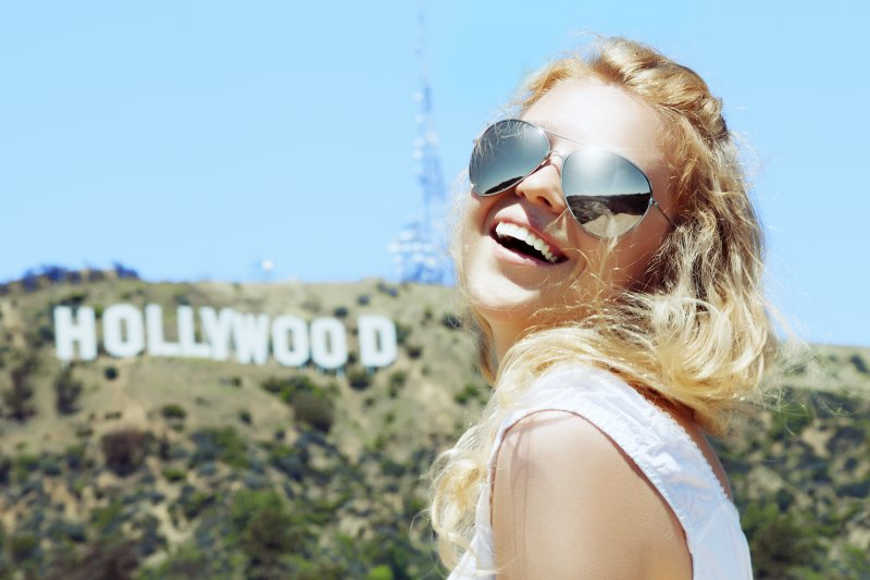 girl smiling in front of the Hollywood sign
